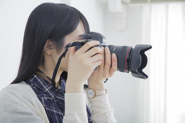 両手でカメラを持って撮影する